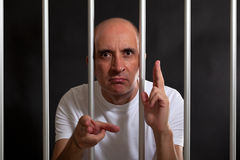 Man in jail gesturing guns with his hands Royalty Free Stock Image