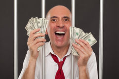 Man in jail laughing with cash Royalty Free Stock Photos