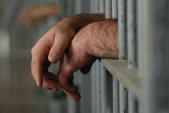 Man in jail or prison. Mans hands behind bars in jail or prison Stock Photo