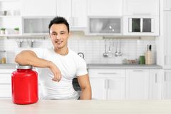 Man with jar of protein shake powder in kitchen. Space for text stock images