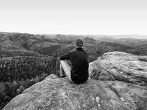 Man in jeans black outdoor sweatshirt and red cap stay at the end of cracked rocky cliff Stock Photos