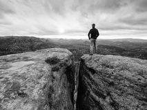 Man in jeans black outdoor sweatshirt and red cap stay at the end of cracked rocky cliff Royalty Free Stock Image