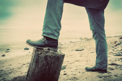 Man in jeans and elegant shoes leaning against trunk tree on wild beach looking at sea. Vintage Stock Images