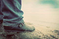 Man in jeans and elegant shoes standing on fallen tree on wild beach looking at sea. Vintage Stock Photo