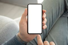 Man in jeans holding phone with an isolated screen. Man hand in jeans holding phone with an isolated screen stock image