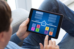 Man in jeans holding tablet with app smart home screen. Man in jeans holding tablet with app smart home on screen Stock Photography