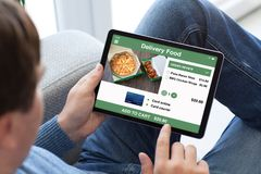 Man in jeans holding tablet computer with app delivery food stock images