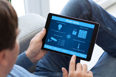 Man in jeans holding tablet computer with smart home Stock Image