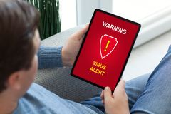 Man hands holding tablet computer with warning virus alert alarm royalty free stock images