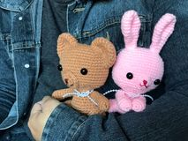 Man in jeans jacket holding cute brown teddy bear and pink bunny crochet dolls Royalty Free Stock Images
