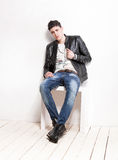Man in jeans and leather jacket relaxing on white wooden chair Stock Images