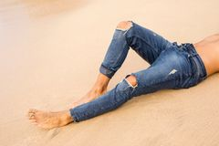Man in jeans lying in sand stock photos
