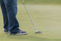 Man in jeans putting golf ball Royalty Free Stock Photo