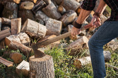 Man in jeans and shirt standing near stump with ax in hands Stock Photography