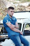 Man in jeans, sitting on an old damaged car Royalty Free Stock Photo