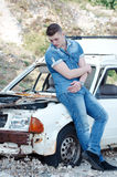 Man in jeans, sitting on an old damaged car Stock Photos