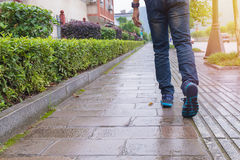 Man jeans and sneaker shoes walking on footpath Stock Photo