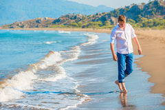 Man in jeans and a white shirt walking. Along the seashore Royalty Free Stock Photography