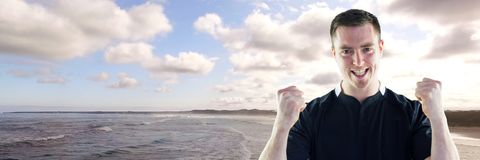 Man in jersey celebrating against coastline. Digital composite of Man in jersey celebrating against coastline Royalty Free Stock Images