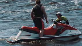 Man on jet ski rides around surfer boy and his coach who floats in water stock video footage