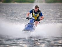 Man on jet ski rides fast. Man on jet ski in the river skims along skims along very fast Stock Photography