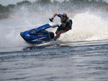 Man on jet ski in the river. Turns with much splashes Royalty Free Stock Photos