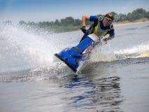 Man on jet ski skims along camera. Man on jet ski in the river skims along camera Stock Image
