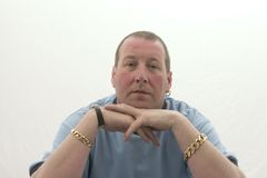 Man with Jewellery. Middle aged male portrait,looking straight to camera wearing heavy jewellery royalty free stock photos