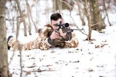 Man jägareskytte med ett prickskyttgevär som siktar och avfyrar kulor Arkivbild