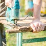 Man with jigsaw repairing bench Stock Photo