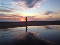 Man jogger running on sunset beach with reflection. Fitness and healthy life concept Royalty Free Stock Photo
