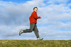 Man jogging. A handsome forties man is smiling as he takes a run along a grassy bank Stock Photos