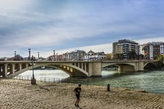 A man jogging along Canal Alfonso XII after San Telmo Bridge stock photos