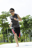 Man jogging barefoot. A young Asian man jogging barefoot at a public park royalty free stock photography