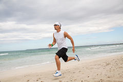 Man is jogging on the beach summertime sport fitness Royalty Free Stock Photos