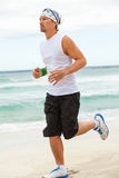 Man is jogging on the beach summertime sport fitness Stock Image