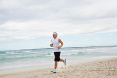 Man is jogging on the beach summertime sport fitness Stock Images