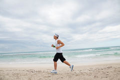 Man is jogging on the beach summertime sport fitness Stock Photography