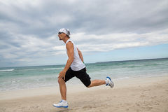 Man is jogging on the beach summertime sport fitness Royalty Free Stock Image
