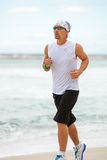 Man is jogging on the beach summertime sport fitness Stock Photos