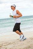 Man is jogging on the beach summertime sport fitness Royalty Free Stock Images