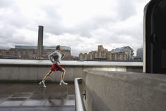 Man Jogging On Bridge Against Building Royalty Free Stock Photos