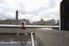 Man Jogging On Bridge Against Building Royalty Free Stock Photos