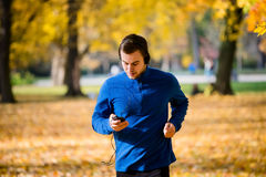 Man jogging and checking mobile phone stock image