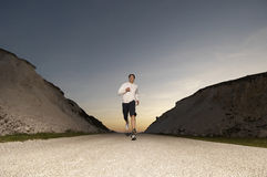 Man Jogging On Country Street At Dusk Royalty Free Stock Photos