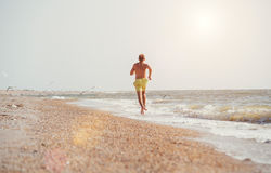 Man jogging on the desert sea line at the morning time Royalty Free Stock Photo