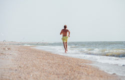Man jogging on the desert sea line at the morning time Stock Image