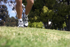 Man jogging on grass in park, low section, surface level, focus on trainers Stock Image