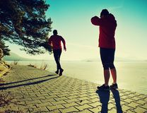 Man jogging at his girlfriend at river bank.  Hills with hot Sun stock photo