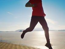 Man jogging at his girlfriend at river bank.  Hills with hot Sun royalty free stock photography